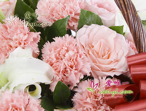 basket of flowers composed of pink roses, pink carnations and white perfume lilies