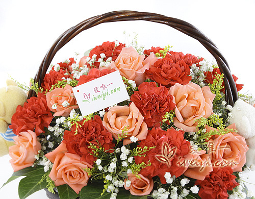 basket of pink roses and red carnations